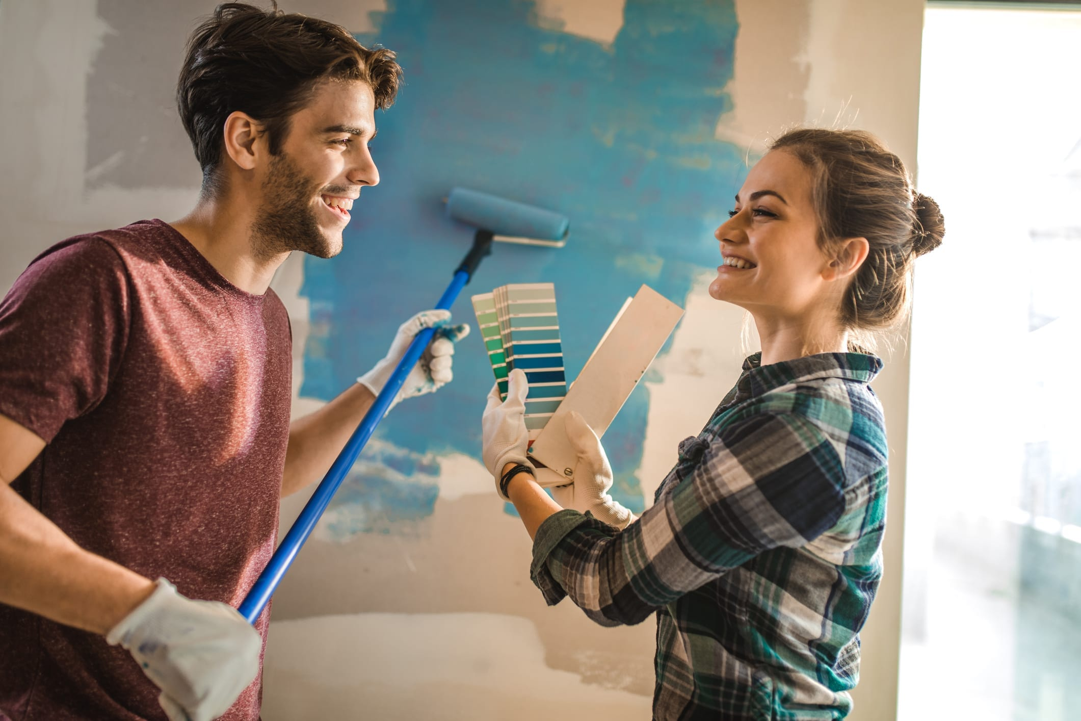 Young couple talking while choosing the right color for their wall in new apartment.